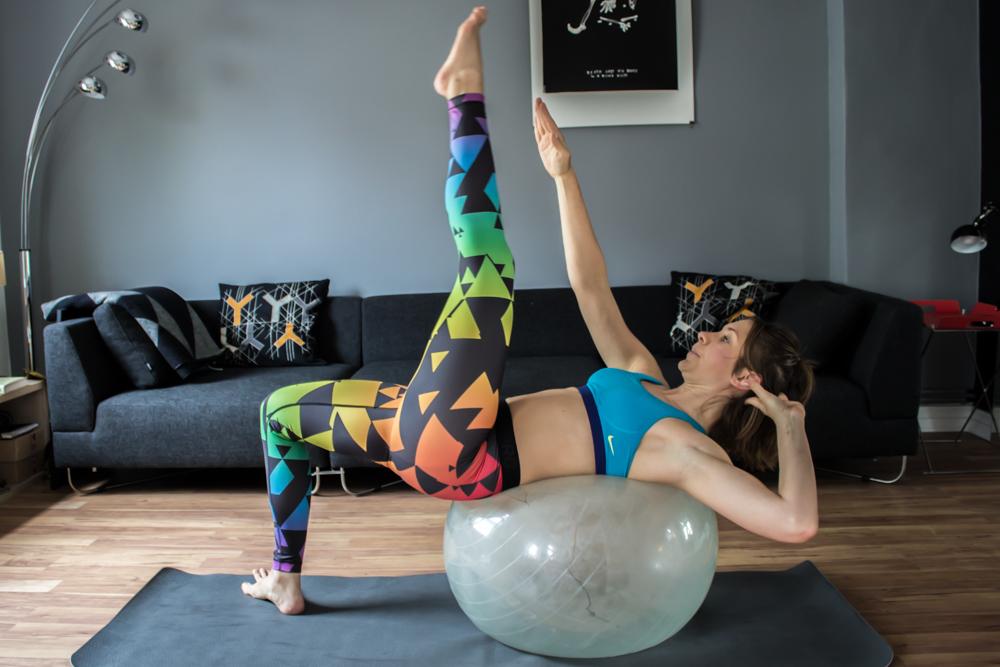 Diagonaler Chrunch mit ausgestreckten Beinen auf Gymnstikball für die schräge Bauchmuskulatur