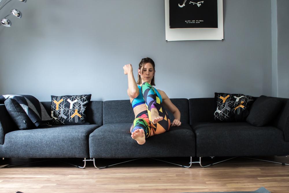 Diagonaler Knee to Elbow auf dem Sofa - Bauchmuskeltraining im Wohnzimmer